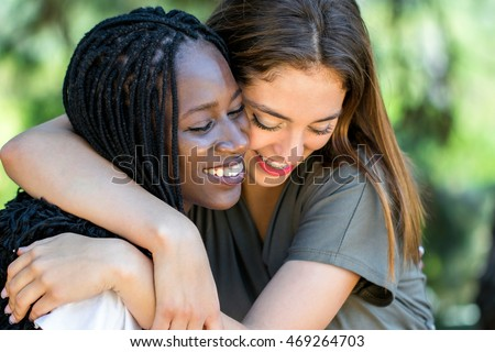 Close up face shot portrait of two multiracial friends showing affection outdoors.