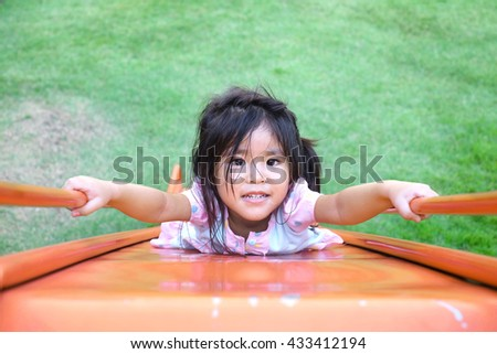 close up face thai girl play slider in outdoor play park