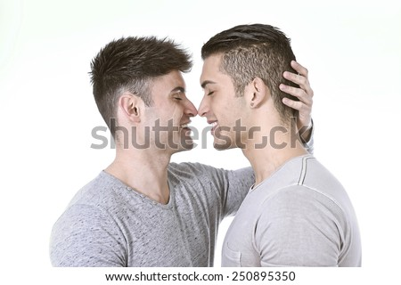 close up faces and expression of happy gay homosexual couple of young attractive and handsome men in love kissing isolated on white background celebrating valentines  - stock photo