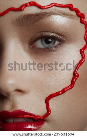 Close up facial beauty portrait of young women with red lipstick, red line on face looking at you white background  - stock photo
