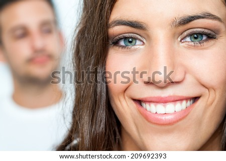 Close up Facial portrait of attractive girl with toothy smile and boy in background.