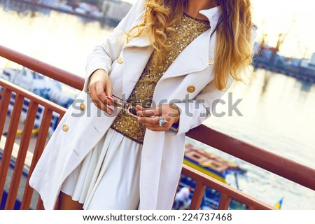 Close up fashion image of woman wearing stylish fall outfit, white mini skirt cashmere coat, golden top and sunglasses, amazing view on sea port, soft evening light. - stock photo
