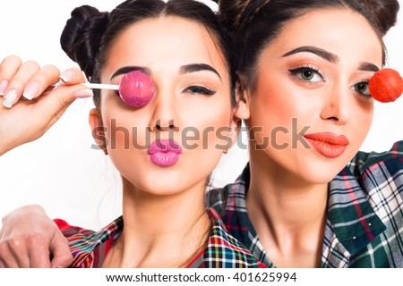 Close up fashion lifestyle portrait  two teen girls,attractive fancy friends in colorful hipster fashionable outfit .Women holding pink lolly pop and having fun together at white background.Isolated   - stock photo