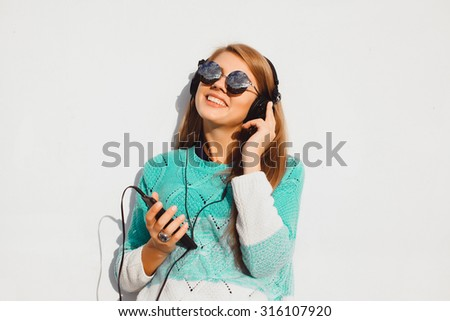 Close up fashion lifestyle summer image of sexy woman with amazing smile, hipster glasses, fashion black earphones, light fresh colors.Black round sunglasses,music player Outdoor sunny portrait  - stock photo