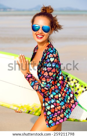 Close up fashion lifestyle summer portrait of stunning sexy surfer woman, wearing bright outfit makeup and sunglasses. Holding surf board s,killing and having fun alone. - stock photo