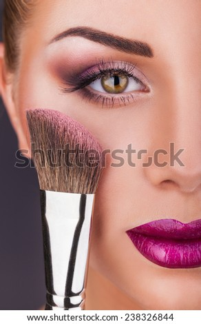 Close-up fashion make-up. Beautiful young woman with makeup brush - stock photo