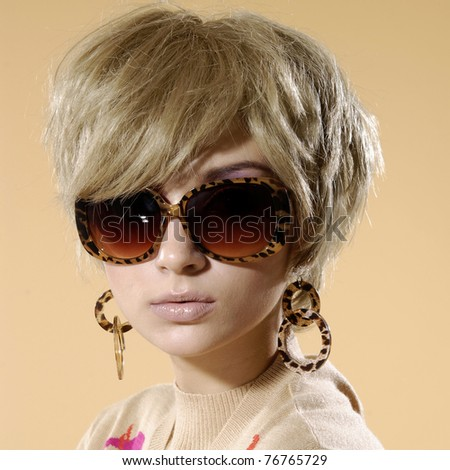 Close up fashion model wearing sunglasses- beige background