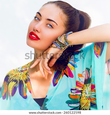 Close up fashion outdoor portrait of elegant   sensual woman  with red lips in bright blue  boho dress and colorful stylish accessories.  - stock photo