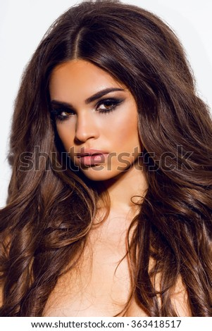 Close up fashion photo of young woman with beauty long curly hair. Fashion model posing at studio. Bright evening make up, tan perfect skin, amazing wavy healthy  hair.