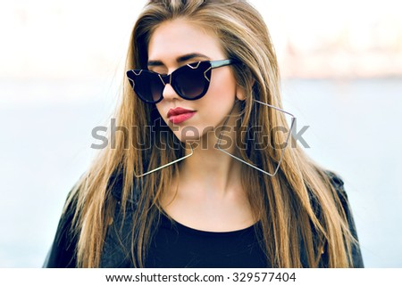 Close up fashion portrait of amazing beautiful woman with fluffy blonde hairs, vintage vat eye sunglasses, soft toned film colors, cold weather sad mood. - stock photo