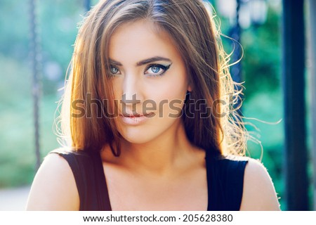 Close up fashion portrait of beautiful blonde woman posing on the street in the evening sunlight. - stock photo