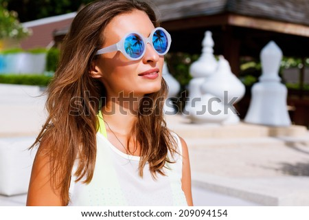 Close up fashion portrait of beautiful brunette girl with perfect bronze skin, wearing trendy round mirrored sunglasses, light background. - stock photo