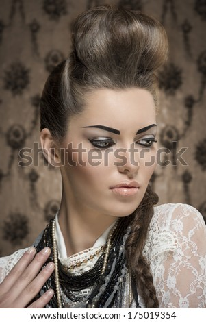 close-up fashion portrait of charming female with creative look, cute brunette hair-style and strong make-up. Wearing white lace shirt and a lot of necklaces - stock photo
