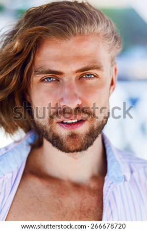 Close up fashion portrait of handsome man with  blonde hair  looking  in the camera.