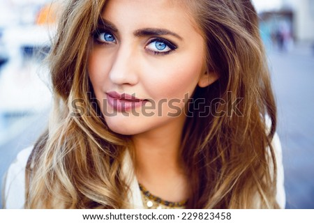 Close up fashion portrait of seductive sexy woman with big blue eyes ,full lips , prefect skin and long fluffy curled hairstyle. Natural make up. - stock photo