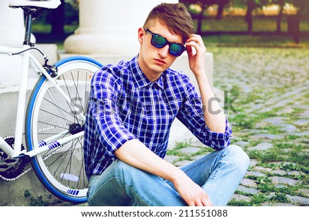 Close up fashion portrait of stylish handsome hipster guy sitting at city park near his fixed bike, wearing blue plaid shirt and mirrored sunglasses. - stock photo