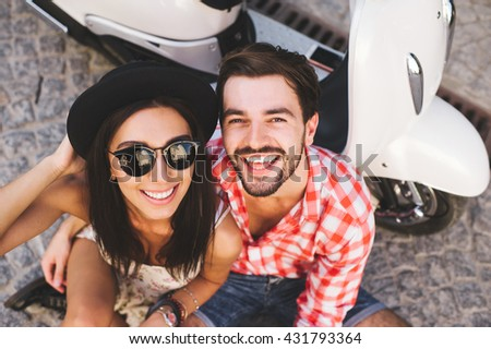 Close up fashion portrait of stylish young couple pretty woman and handsome man posing near a vintage scooter on a summer day - stock photo