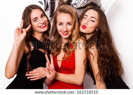 Close up fashion portrait of  three  elegant women  with bright make up, curly hair and elegant evening dress smiling show kiss and having fun against white background. - stock photo