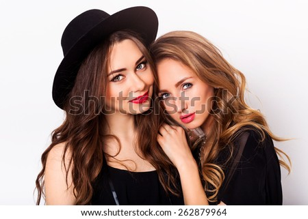 Close up fashion portrait of two elegant stylish women wearing a leather skirt and black hat , holding retro camera. Posing against white background.They smiling and looking at camera. - stock photo