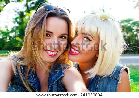 Close up fashion portrait of two pretty friends in the park . Girls having fun   and makes selfie. - stock photo