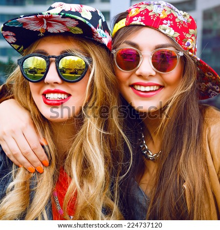 Close up fashion portrait of two sisters hugs and having fun together, wearing bright floral hats and stylish mirrored sunglasses, best fiend enjoy amazing time together. - stock photo