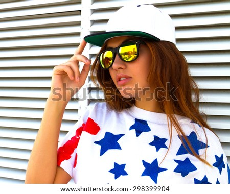 Close up fashion portrait of young attractive woman wearing t-shirt with american print and swag hat. Trendy lifestyle portrait of stunning hipster stylish girl posing white urban background. - stock photo