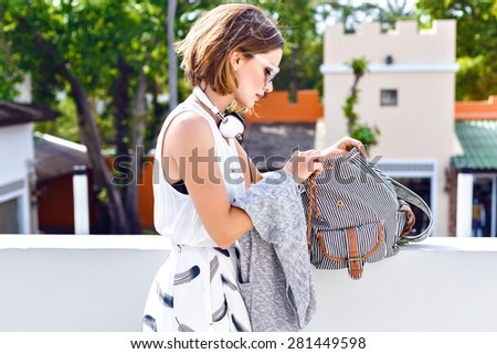 Close up fashion portrait of young hipster pretty woman, searching something at her backpack, walking and having fun at shopping center. - stock photo