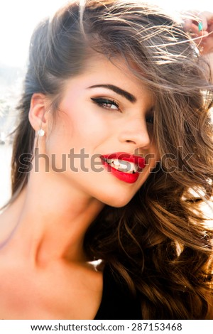 Close up fashion portrait of young sexy sensual seductive woman with perfect fluffy curled brunette hairs amazing smile and big blue eyes.Perfect make-up,Attractive woman face,Tan model,luxury style - stock photo