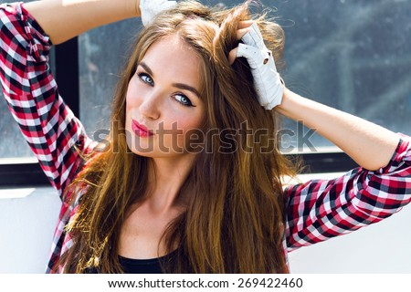 Close up fashion  portrait of young sexy stunning sensual woman with long brunette hairs perfect skin and bright make up, wearing clear hipster vintage glasses, plaid shirt and making kiss. - stock photo
