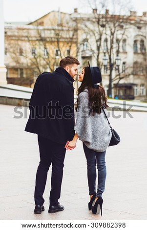 Close up fashion portrait of young stylish glamour girl and guy in love . Couple walking down the street in sunny fall . Warm autumn colors. Wearing black trendy outfit .