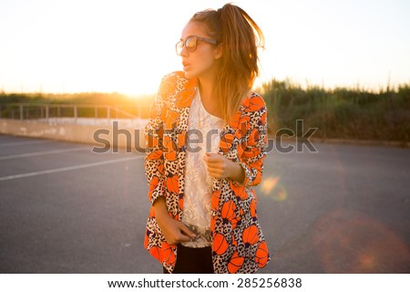 Close-up fashion portrait of young stylish hipster girl posing at sunset.Free happy woman,in trendy summer outfit.Young adult enjoying breathing freely fresh air.Urban background,fashionista,blogger - stock photo
