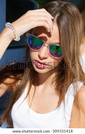 Close up fashion portrait of young woman. Close up fashion portrait of pretty hipster teenage girl with long brunette hairs, wearing stylish trendy mirrored blue sunglasses, bright colors.  - stock photo
