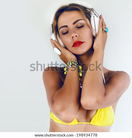 Close up fashion portray of young pretty woman in bright yellow bikini listening music in her modern stylish white headphones and really enjoy soundtrack. White background, not isolated. - stock photo