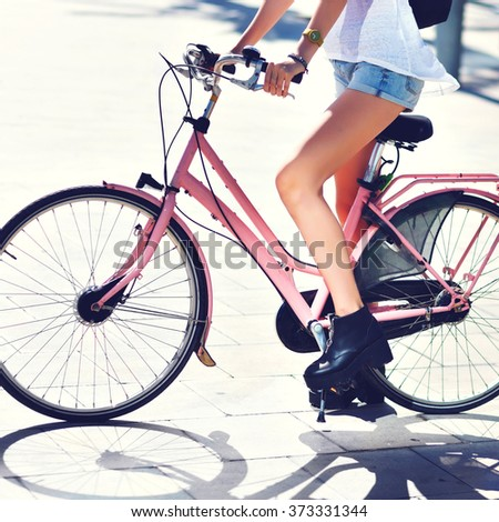 Close up fashion street style details, woman legs , later boots and mini shorts, riding hipster vintage bicycle, toned colors, summer sunny days, freedom, travel, joy. - stock photo