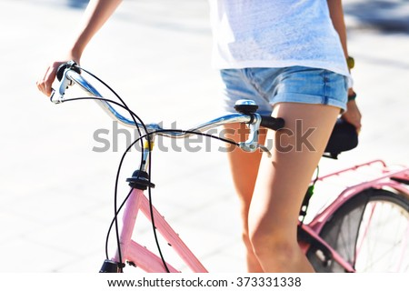 Close up fashion street style details, woman legs , mini shorts, riding hipster vintage bicycle, toned colors, summer sunny days, freedom, travel, joy. - stock photo