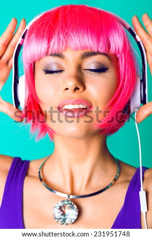 Close up fashion studio portrait of sexy beautiful young woman wearing massive diamond trendy necklace and pink party wig, listening her favorite songs close her eyes and fell the music. - stock photo