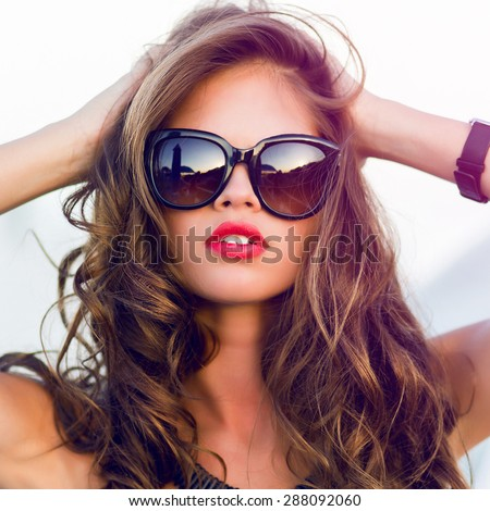 Close up fashion  summer  portrait of stylish  sexy  woman with perfect  tanned fit body   wearing trendy sunglasses drinking cocktail and  enjoying  pool party on luxury villa.  - stock photo