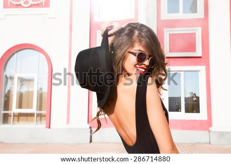 Close-up Fashion woman portrait of young pretty trendy girl posing at the city in Europe,summer street fashion,holding retro fedora hat popular until the 60s.laughing and smiling portrait.trendy chic - stock photo