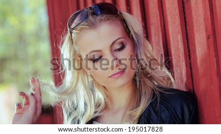 Close up, fashionable beautiful young blond wearing a leather jacket and leans against the red wall - stock photo