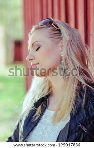Close-up, fashionable beautiful young blond wearing a leather jacket and leans against the red wall - stock photo