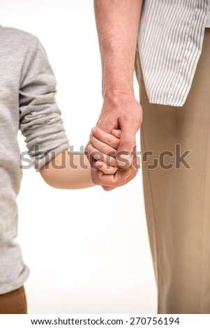 Close-up. Father and son holding hands, isolated a white background.