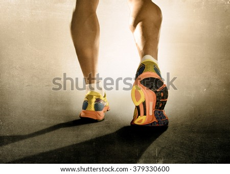 close up  feet with running shoes and strong athletic legs of sport man jogging in fitness training workout isolated on grunge harsh background design in advertising poster style - stock photo