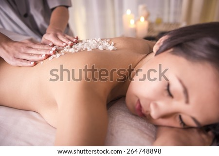 Close-up. Female getting a salt scrub beauty treatment in the health spa. - stock photo