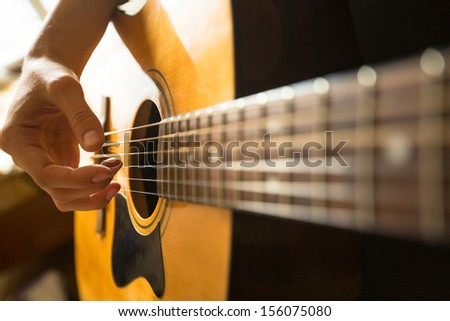 Close-up female hand playing on acoustic guitar.  - stock photo