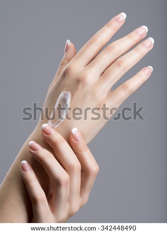 Close-up female hands applly hand cream.  with french manicure on nails - stock photo
