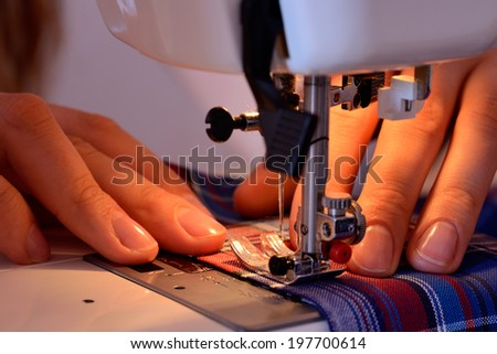 Close-up female hands sewing fabric on sewing machine - stock photo