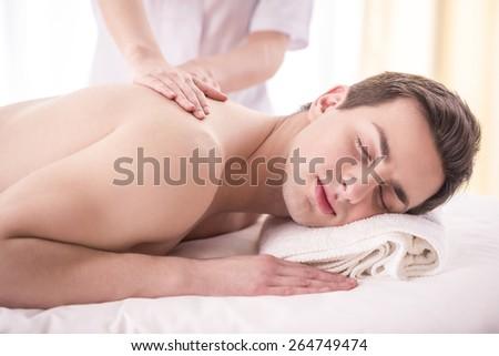 Close-up. Female masseur doing massage on male in the spa salon.