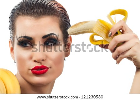 Close-up female pointing peeled banana on her head - stock photo