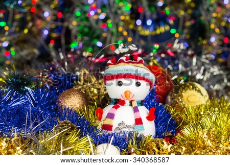 Close-up festive snowman with Christmas balls and tinsel on blurred lights background