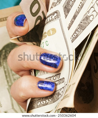 close up fingers with blue creative pattern manicure holding dollars, indigo design - stock photo